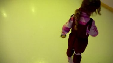 Little girl skates on ice rink, colored light flashes — Stock Video