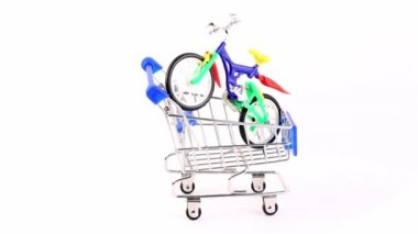 Toy bicycle is in shopping cart, composition rotates — Stock Video