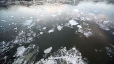 Sail through ice in river, which reflects forest on shore — Stock Video