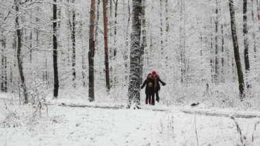 Two girls run closer in woods where all covered with first snow
