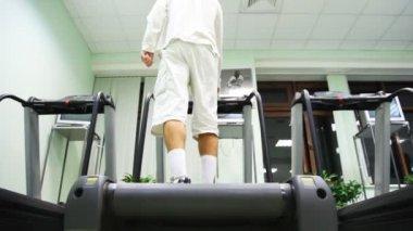 Soporte de hombre en caminadora en gimnasio, se enciende y comienza a ir — Vídeo de Stock