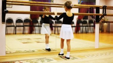 Little girl does ballet leg movements while facing mirror in hall — Stock Video