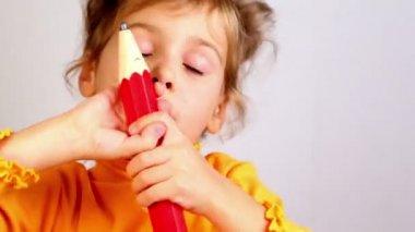 Dziewczynka posiadają duży ołówek i uśmiech — Wideo stockowe