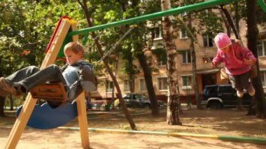 Boy and little girl sway on swing at playground — Stock Video