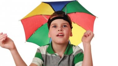 Boy in cap as umbrella rainbow colors fun pretend that hiding from rain — Stock Video