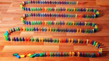 Many colored dominoes built zigzag on parquet — Stock Video