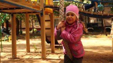 Niña cuelga de la cuerda en el patio de recreo y balanceo — Vídeo de stock