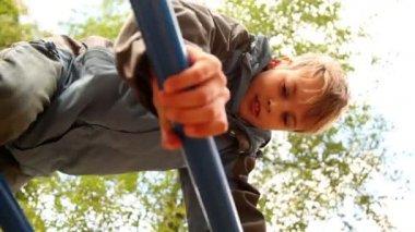 Chico suba las escaleras en el patio de recreo — Vídeo de stock