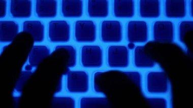 Tipo oscuro dedos en el teclado con retroiluminación azul y botones naranjas — Vídeo de stock