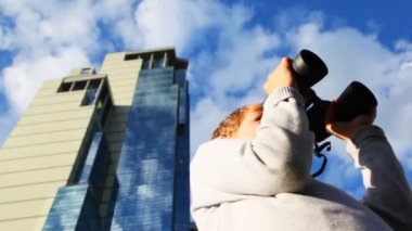 Inquisitive boy looks through binoculars and turns on background of skyscrapers — Stock Video