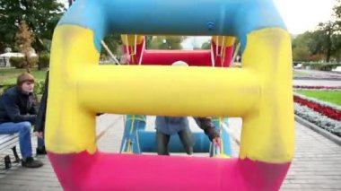 Boy walk in inflated wheel in park at Bolotnaya square — Stock Video