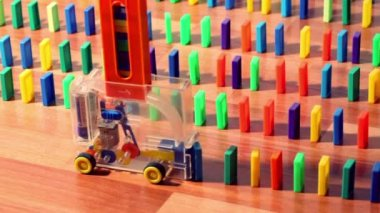 Man turn on toy machine wich begin moves and put domino blocks — Stock Video