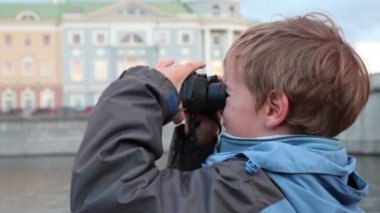 Boy stands on waterfront, looking through binoculars — Stock Video
