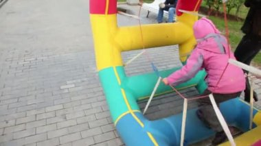 Girl walk in inflated wheel in park at autumn day at Bolotnaya square — Vídeo Stock