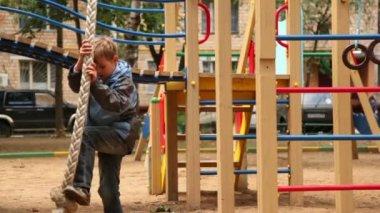 Pojken klättrar på repet på lekplats — Stockvideo
