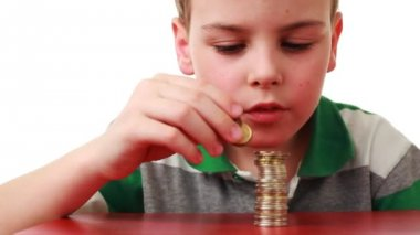 Boy takes off coins placed column and puts it on red base — Stock Video