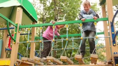 Little girl and boy rock on hang down steps at playground — Stock Video