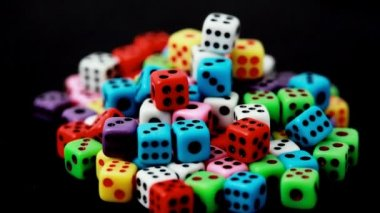 Many colorful dice stacked in hill rotate on black — Stock Video