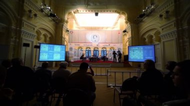 People watch chess tournament, current positions at chessboards are shown on screens — Stock Video