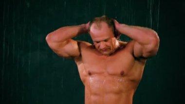 Bodybuilder stands under water jets, wash his body — Stock Video