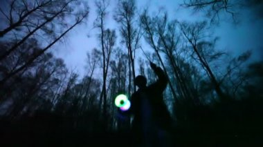 Man plays glowing toy in the dark forest, short exposure — Stock Video