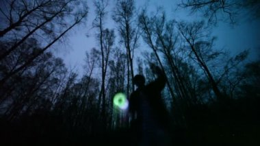 Man plays glowing toy in the dark forest, long exposure — Stock Video