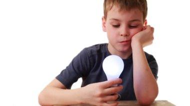 Niño en la mano sostiene bombilla que milagrosamente luces, está asombrado — Vídeo de stock