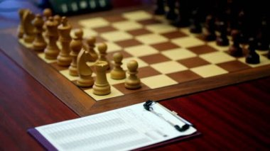 Hand arranges figures on chessboard, paper for log moves lay on table — Stock Video