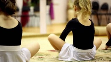 Little girls sit on floor and streches risen legs, view from behind — Stock Video