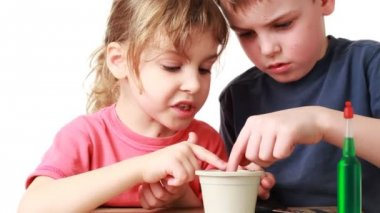 Boy and little girl put in pot with soil seed plants — Stock Video