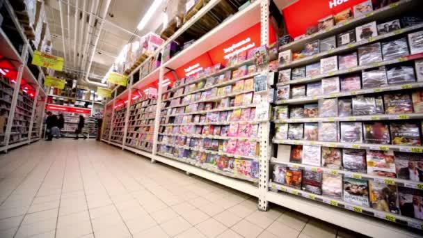 Vitrine avec des disques dvd avec varius films dans l'hypermarché auchan — Vidéo