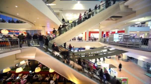 Beaucoup de gens se déplacent sur des escaliers mécaniques dans l'atrium de centre commercial plusieurs étages — Vidéo