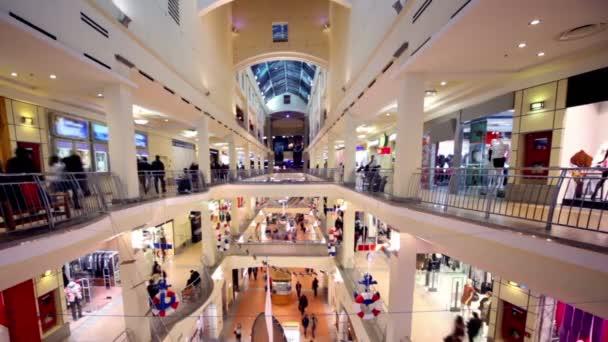 Les gens marchent le long des boutiques sur l'atrium de centre commercial plusieurs étages — Vidéo