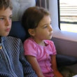 Stock Video: Little girl and boy travel by fast train, time lapse