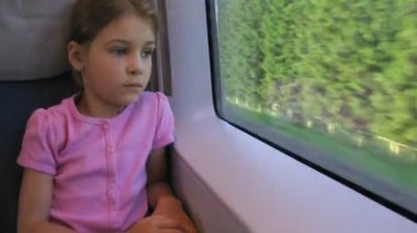 Girl looks through window in moving train, time lapse — Stock Video