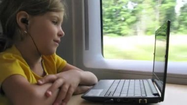 Girl watch video on notebook while travelling by train, time lapse — Stock Video