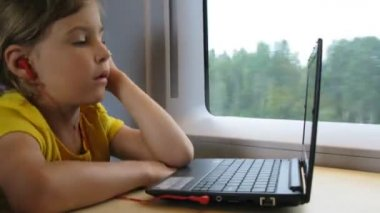 Girl in headphones watch video on notebook while travelling by train — Stock Video