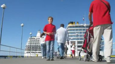 Boy standing on stones near bay in front of cruise liners — Stock Video