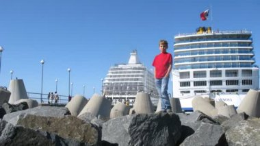 Boy playing in front of cruise liners stationed at bay — Stock Video