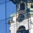 Clock in tower of monastery Stiftskirche are reflected in glass wall — Stock Video