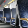 Dark blue chairs with yellow armrests stand in carriage of train — Stock Video