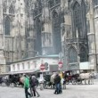 Stock Video: Tourists walk and are photographed in front of Stephansdom