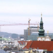 Stock Video: Towers of Jesuit church stand near cranes against roofs of houses