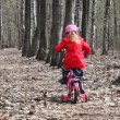 Little girl goes away on bicycle at park — Stock Video