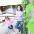 Stock Video: Mother and her kids walk upstairs by spiral stairway with plants on wall in multiple floor building