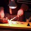 Hands of cook knife big piece of smoking meat by light of lamp — Stock Video