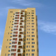 High-rise building of yellow color stands against blue sky — Stock Video