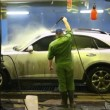Two workers wash car indoors strong streams of water — Stock Video