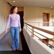 Stock Video: Young womwalks along corridor in multiple floor building