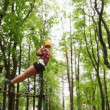Stock Video: Girl moves down downwards suspended on cable in wood between trees